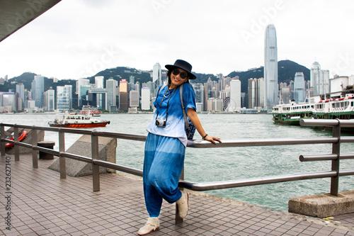 Fototapeta premium Podróżujący tajska kobieta pozuje do zrobienia zdjęcia z widokiem na krajobraz i panoramę wyspy Hongkong na molo w porcie Wiktorii