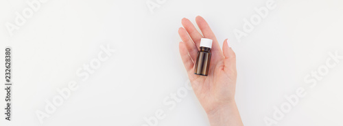 Photo  Woman hand with small glass bottle isolated