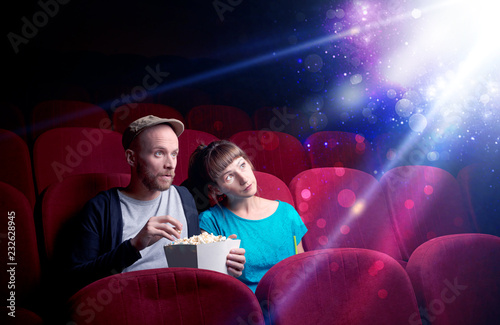 Fotografía  Romantic couple cuddling and watching the miraculous part of the film