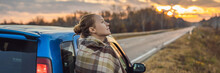 A Woman In A Plaid Stands By The Car On The Side Of The Road In The Background Of The Dawn. Road Trip Concept BANNER, LONG FORMAT