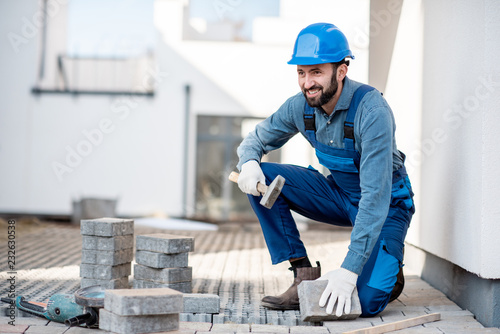 Builder in uniform laying paving tiles on the construction site with white house Canvas