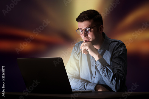 Fotografie, Obraz  Young handsome businessman working late at night in the office with warm lights