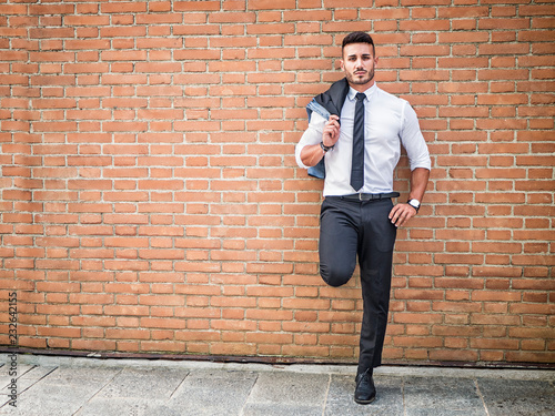 Fotografía Portrait of stylish young man wearing business suit, standing in modern city set