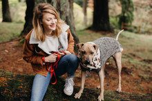 Woman Snuggling Her Dog In A Sweater