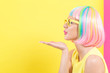 Woman in a colorful wig blowing a kiss on a split yellow and pink background