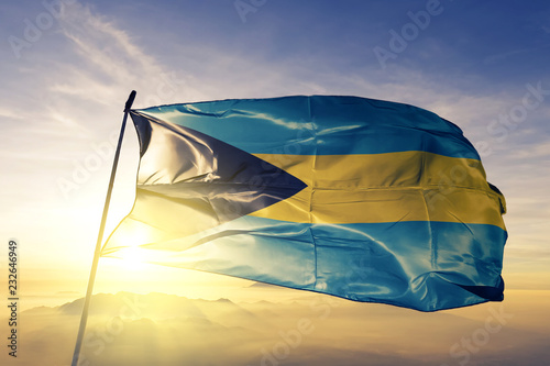 Fotobehang Zonsondergang Bahamas Bahamian flag textile cloth fabric waving on the top sunrise mist fog
