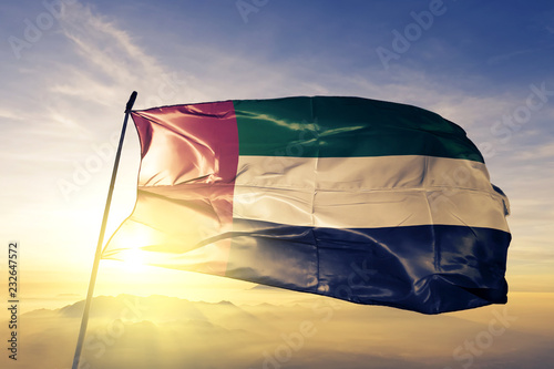Fotomural  United Arab Emirates flag textile cloth fabric waving on the top sunrise mist fo