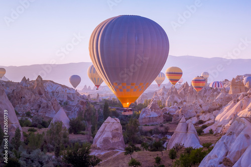 Hot air balloons flying in beautiful Cappadocia hilly landscape, amazing tourism Canvas Print