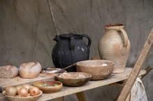 Pottery Ale Jugs, And Wooden Bowls On A Table As Part Of A Display Of Historical Food.