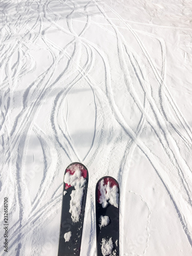 Skis and tracks in fresh snow, viewed from above