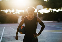 Portrait Of Black Man Playing Basketball On Outdoor Court.