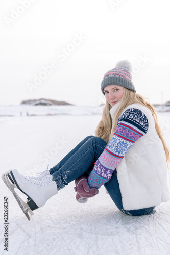 Woman in skates sitting on ice