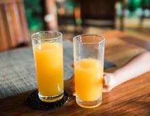 Two Glasses Of Fresh Orange Juice, One Half Finished