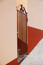 An Iron Gate In A Colorful Wall