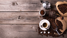On The Rustic Wooden Table A Cup Of Hot Coffee, A Vintage Coffee Grinder, An Italian Moka And Coffee Beans. High Angle View