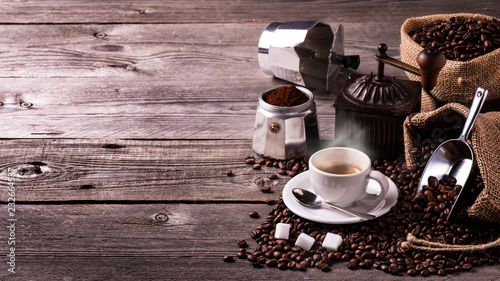Fotografie, Obraz  on the rustic wooden table a cup of hot coffee, a vintage coffee grinder, an Italian moka and coffee beans