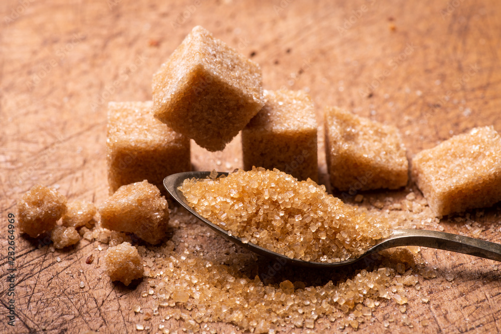 Fototapeta In the foreground, raw cane sugar crystals in the spoon. In the background some sugar cubes