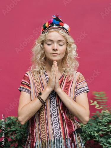 Stylish meditating model on pink
