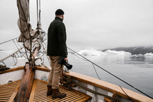 Portrait Of Yang Men, Adventurer, Photographer With Vintage Camera In Hands Dressed Sweater, Rain Coat, Leather Boots, On The Sailing Yacht, Vessel Or Boat In The Ocean With Icebergs On The Background