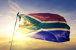 canvas print picture - South Africa african flag textile cloth fabric waving on the top sunrise mist fog