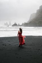 Yang Women In A Red Long Dress Walks On The Black Sand Beach, VIk Iceland