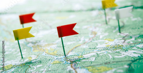 Stampa su Tela  topographic map with colored flag pushpins close up