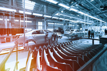 Worker Looks Into Car Body On Production Line. Factory For Production Of Cars In Blue. Modern Automotive Industry. Blue Tone