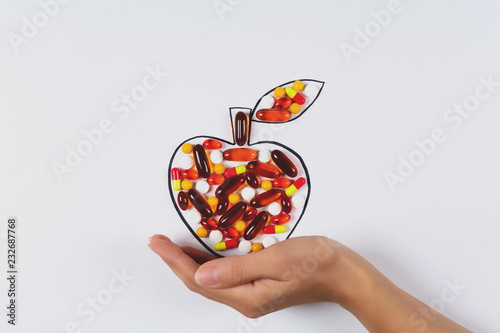 Valokuvatapetti Hand holding drawing apple with colorful capsules and pills on white background