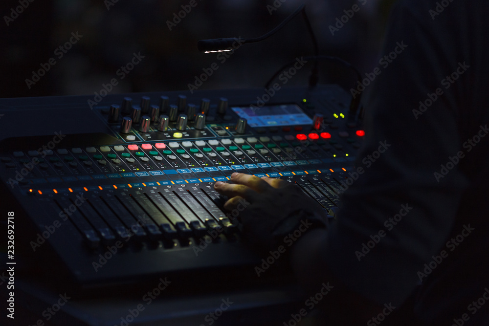 Fototapeta A man hand on a mixing console changing sound volume