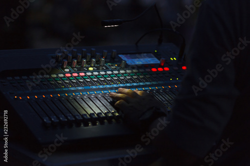 Photo  A man hand on a mixing console changing sound volume