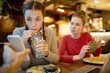 Amazed girl sipping drink through straw while looking at curious video or promo in smartphone of her friend