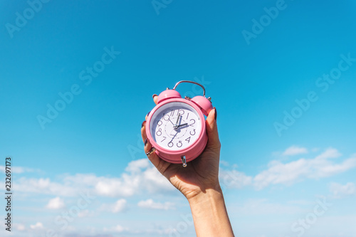 Fotografie, Tablou  Woman's hand is holding pink alarm clock on the sky background