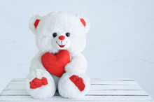 Toy White Bear With A Heart In His Hands. Sits On A Wooden Table.