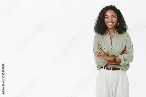 Portrait of enthusiastic delighted adult dark-skinned woman with curly haircut and trendy outfit crossing arms on chest smiling and laughing joyfully talking casually in office during lunch break