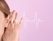 Young Woman With Hearing Problem On Color Background, Closeup. Space For Text