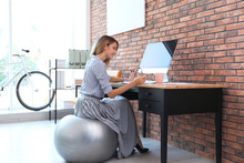 Beautiful Businesswoman Sitting On Fitness Ball At Desk In Office. Workplace Exercises