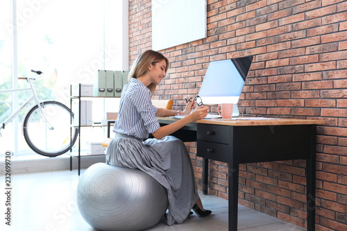 Fényképezés Beautiful businesswoman sitting on fitness ball at desk in office