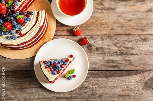 Flat lay composition with delicious red velvet cake and space for text on wooden table
