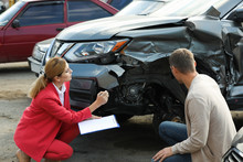 Man Reporting And Insurance Agent Filling Claim Form Near Broken Car Outdoors