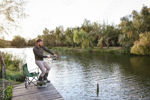 Man with rod fishing on wooden pier at riverside. Recreational activity