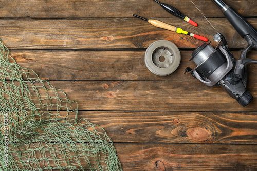Flat lay composition with fishing equipment and space for text on wooden background