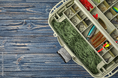 Box of different fishing accessories on wooden background, top view with space for text