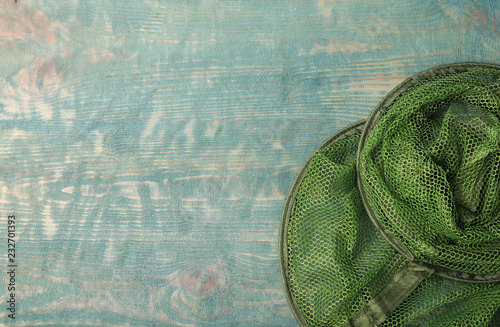 Fishing net on wooden background, top view with space for text