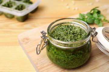 Fototapeta Homemade basil pesto sauce in glass jar on wooden table