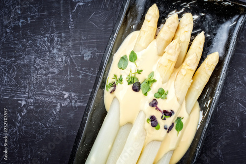 Traditional boiled white asparagus with sauce hollandaise and herbs as top view on a plate with copy space left