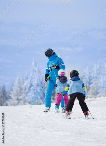 Children with teacher learning skiing