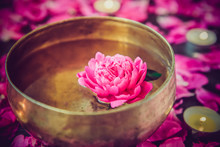 Tibetan Singing Bowl With Floating Inside In Water Pink Peony Flower. Burning Candles And Petals On The Black Stone Background. Meditation And Relax. Exotic Massage. Selective Focus.