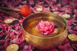 Leinwanddruck Bild - Tibetan singing bowl with floating inside in water pink peony flower. Burning candles, special sticks and petals on the black stone background. Meditation and Relax. Exotic massage. Selective focus.