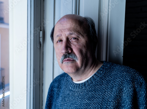 Fotografía  Depressed old man looking through the window feeling alone and unhappy suffering