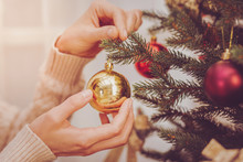 Nice Ornament. The Close Up Of Delicate Female Hands Handing A Golden Bauble On A Christmas Tree While Decorating It For Christmas Celebration